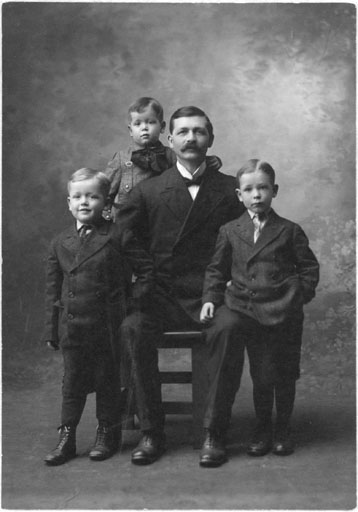 Photograph from about 1907 of Archibald Ralph Collins seated with his three sons around him.  James Cummins Collins is standing on the right, Sterrett Cummins Collins is standing on the left, and John Oliver Collins is standing behind.